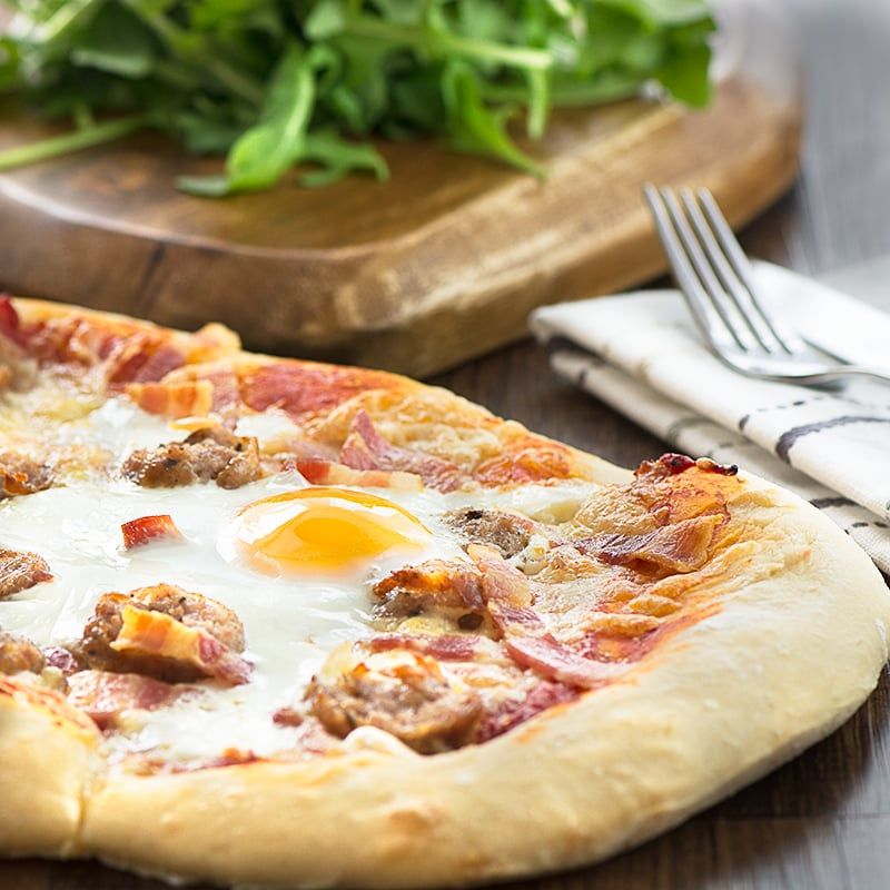 """All-day breakfast pizza - delicious homemade pizza dough topped with sausage, bacon, cheese and even a """"fried"""" egg."""