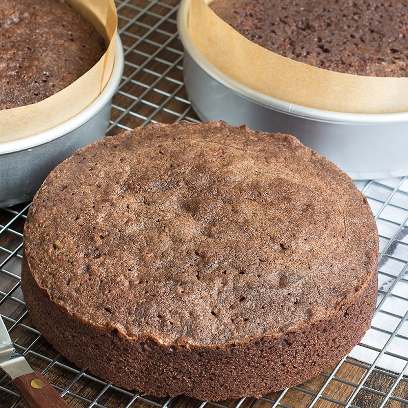 A layer of road chocolate cake on a cooling rack with two more chocolate cakes in tins in the background.