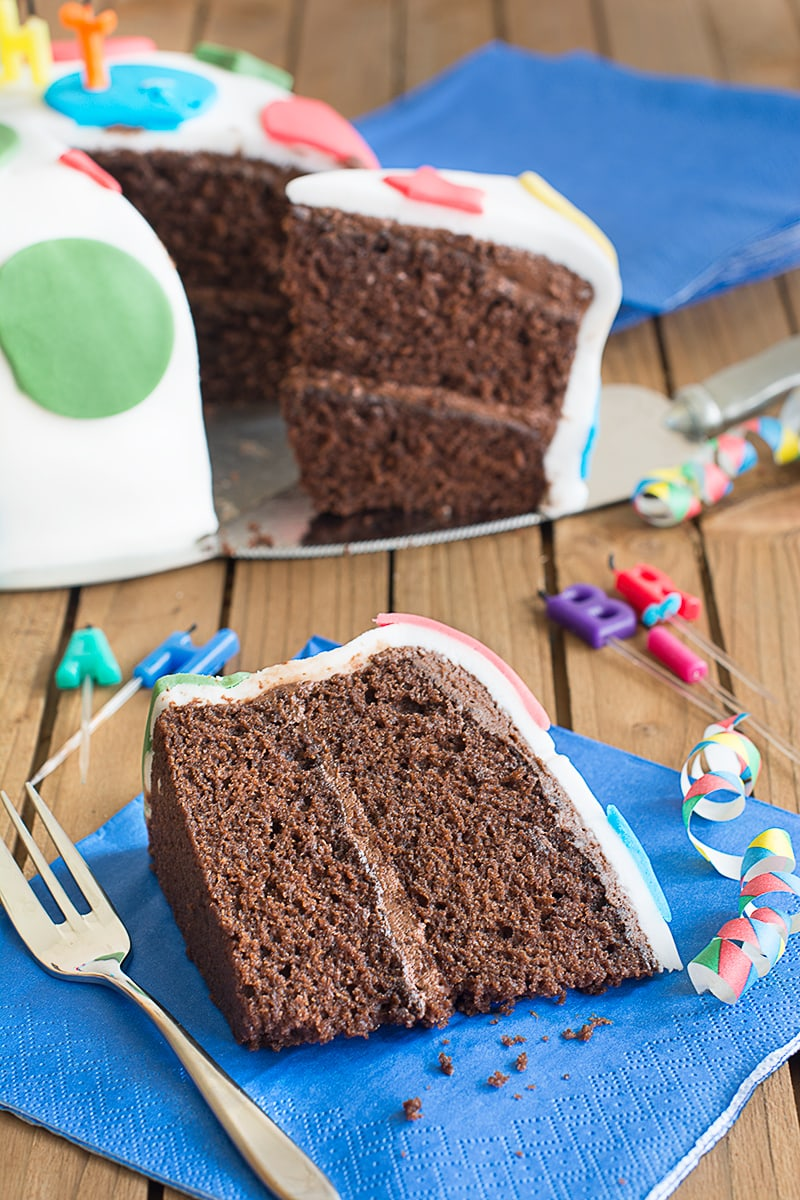 A slice of chocolate birthday cake filled with chocolate buttercream and covered in fondant icing on a blue napkin with a cake fork at the side. There are candles laying just behind it and behind that it the rest of the cake with another slice being removed on a cake slice.