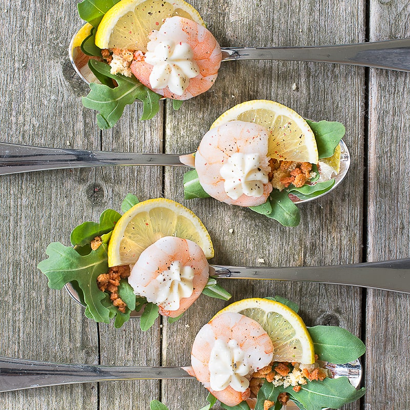 Fresh king prawns with rocket, croutons, bacon, lemon and mayonnaise, all served on a single spoon - perfect for a party.
