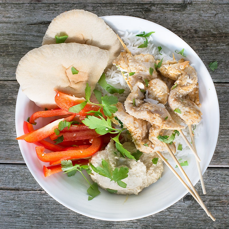 Chicken satay skewers with rice, pitta, hummus and peppers.