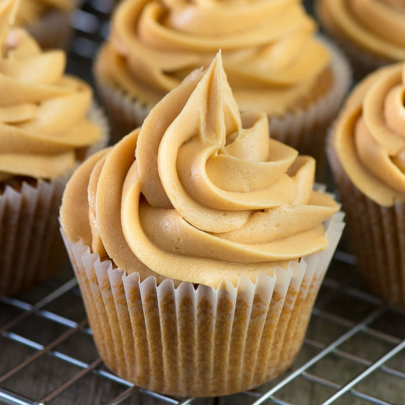 A close up of a caramel cupcake topped with a swirl of caramel buttercream with more cupcakes in the background.