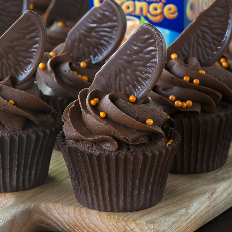 Chocolate orane cupcakes topped with buttercream, chocolate orange and orange sprinkles with a Chocolate Orange in the background.