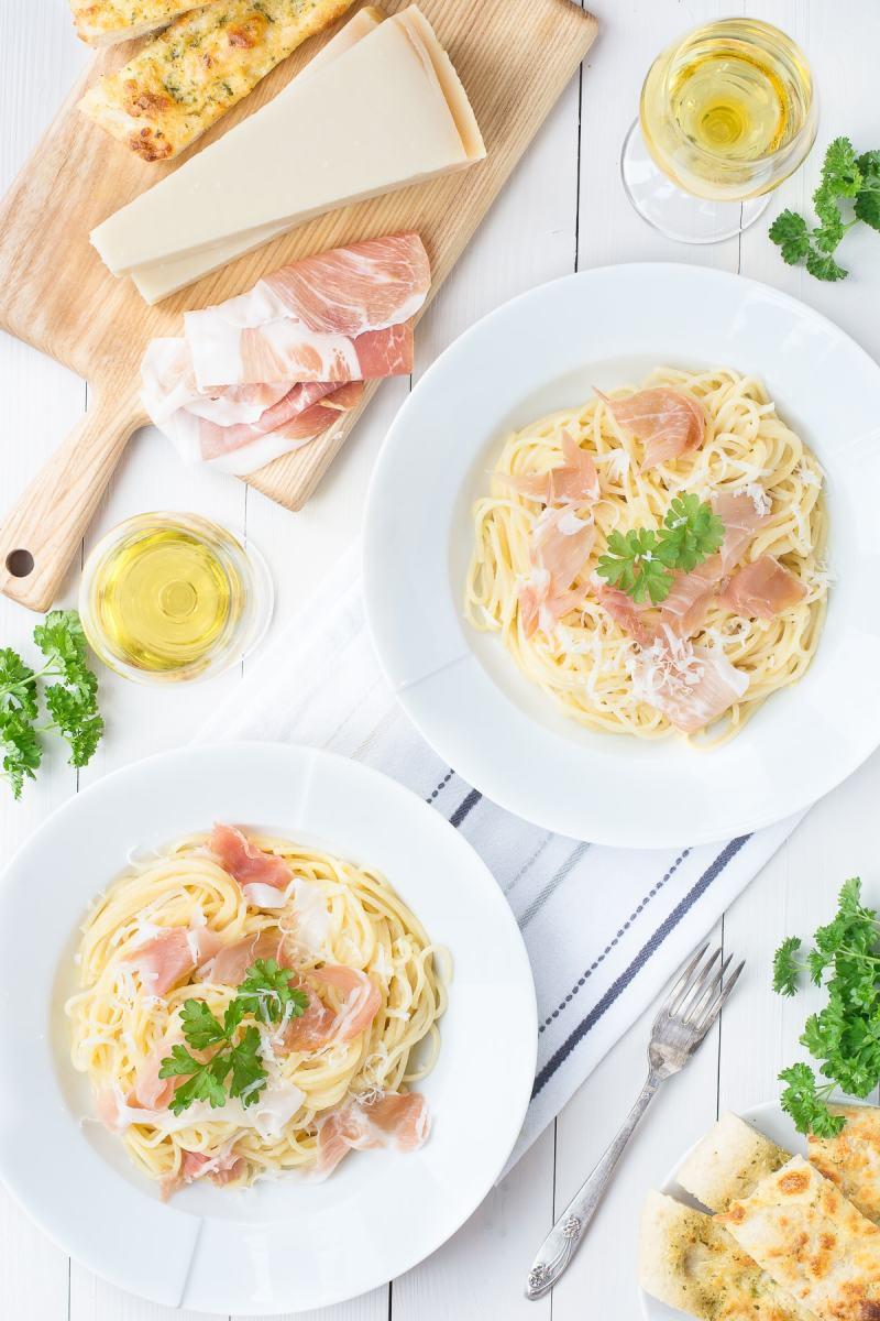 Bowls of delicious, creamy Spaghetti Carbonara made with Prosciutto di San Daniele and Grana Padano cheese. Served with white wine and garlic bread.