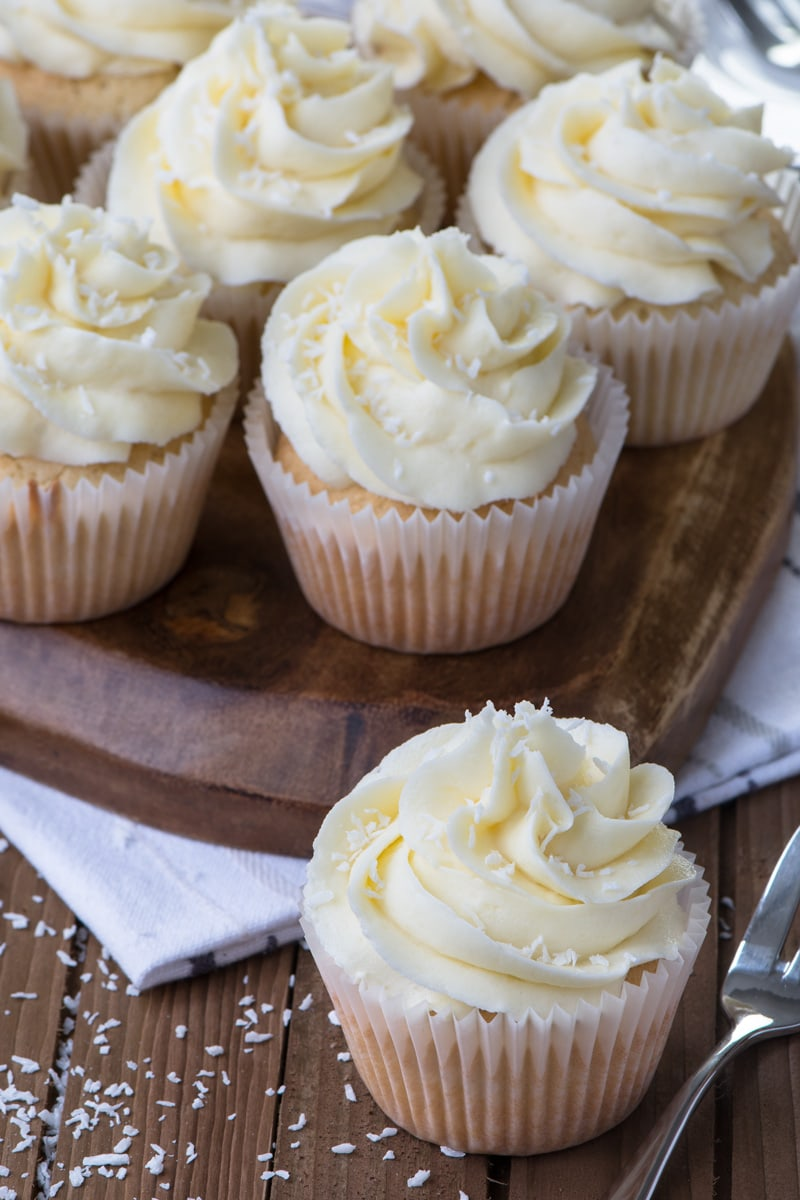 A coconut cupcake topped with coconut buttercream next to a cake fork with more cupcakes on a wooden board in the background.