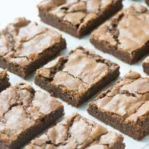 Homemade chocolate brownies cut into squares and arranged in rows. You can see the crisp, shiny top and gooey centre.