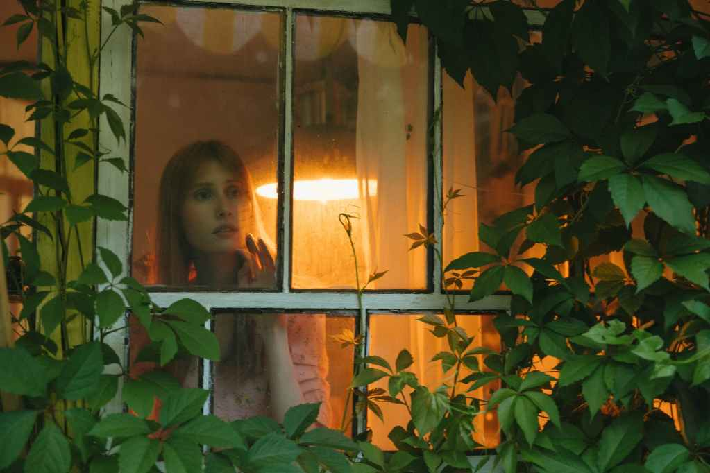woman standing by a glass window looking outside