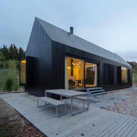 エルフ・アルキテクテンの黒ずんだ木材のコテージをドイツのリゾート地向けにフォーマットする