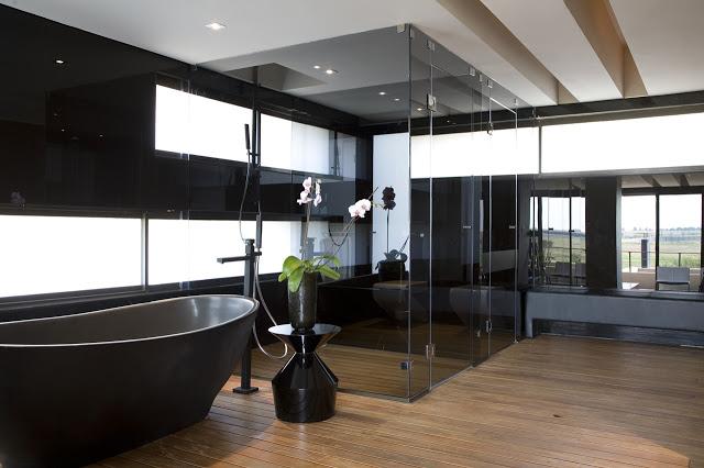 シャワー付きのクールなバスルームのインテリアデザイン南アフリカの大邸宅の間にあるモダンジュエル-セレンゲティハウスバイニコファンデルミューレンアーキテクツ