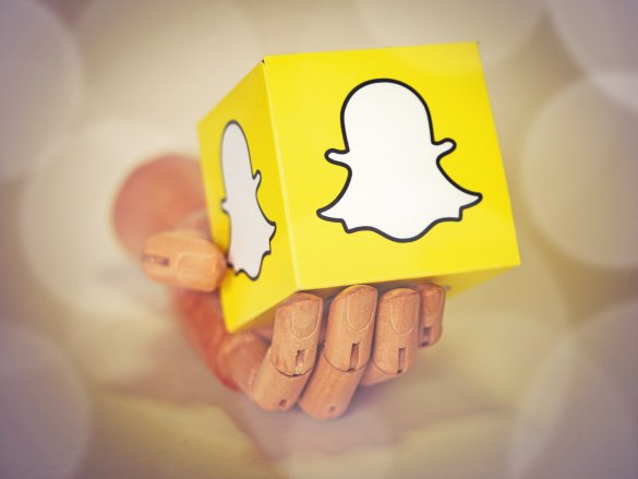 A hand holds a cube with the Snapchat logo