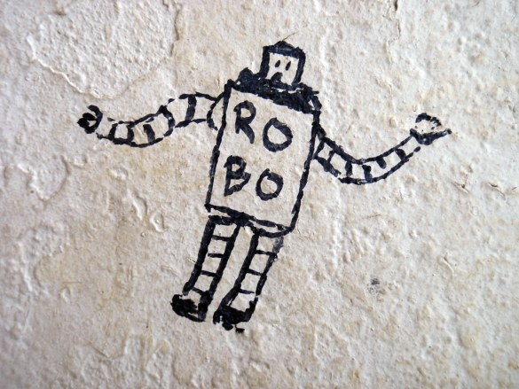 A cartoon drawing of a robot on a plaster wall.