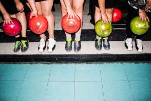 5 people holding bowling balls