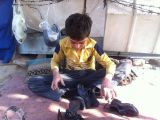 Pathan cobbler boy in a street side shop in Lahore