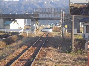 六条駅を紹介します。踏切を横断する車の向こうに見える列車/どこまでもアマチュア