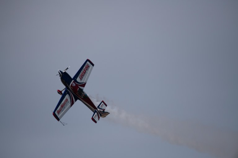 Lucas Oil sponsored airplane with smoke trail, and pilot facing audience.