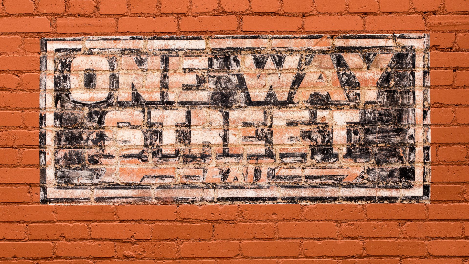One way street painted sign on brick wall.