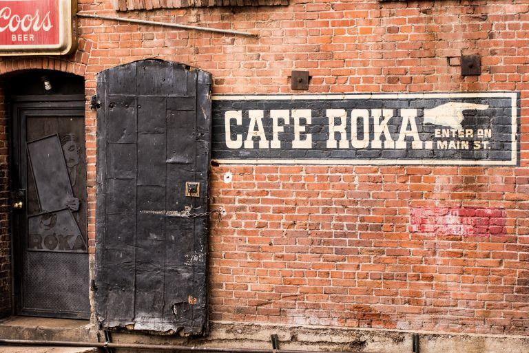 Cafe Roka sign on brick wall.