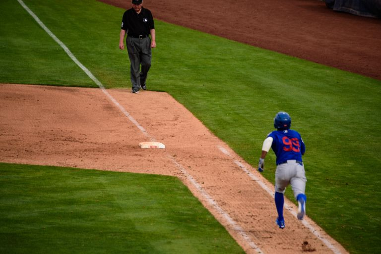 Cubs player heading for first base.