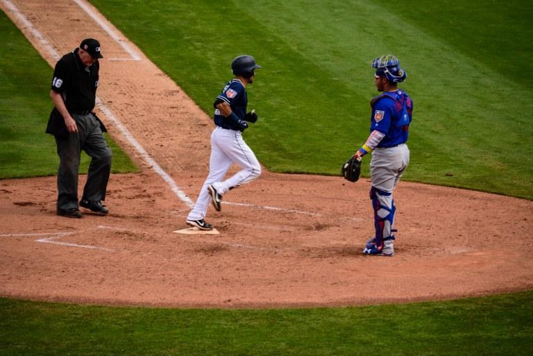 Baseball player touching home plate.