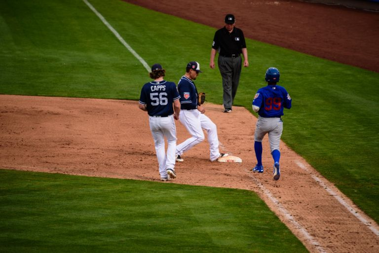 Padres player tagging first base as Cubs player runs to base.