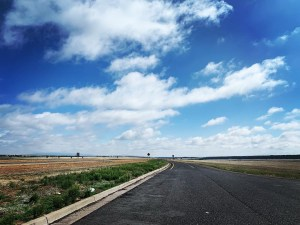 A road, blue skies, and puffy white clouds.