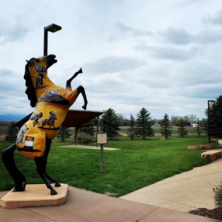 A statue of a yellow horse with Colorado specific drawings of horses on it.