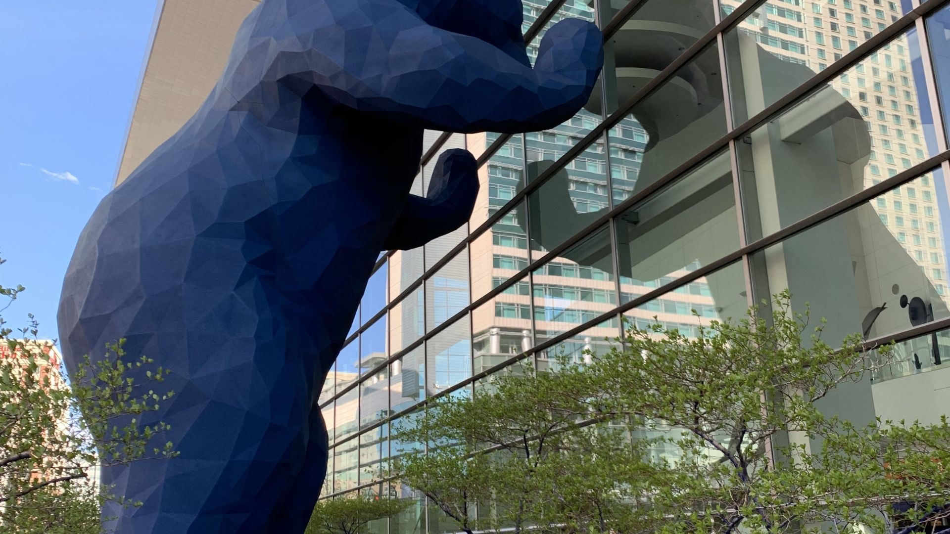 A blue bear statue peeking into the Colorado Convention Center in Denver.