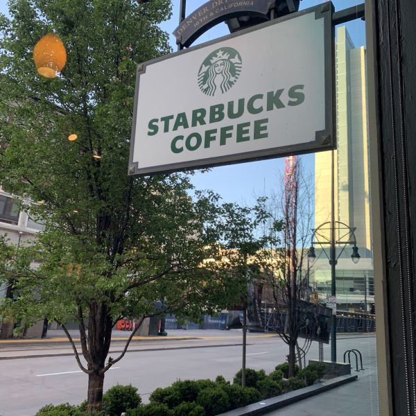 Starbucks sign with Hyatt building in the background.
