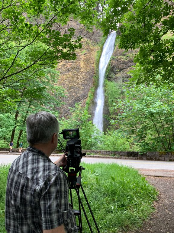 A man behind a video camera with the camera pointed at Horsetail Falls.
