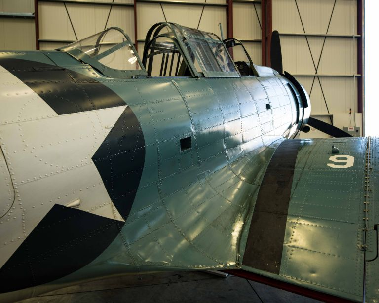 A Douglass SBD Dauntless plane from the behind the right wing.