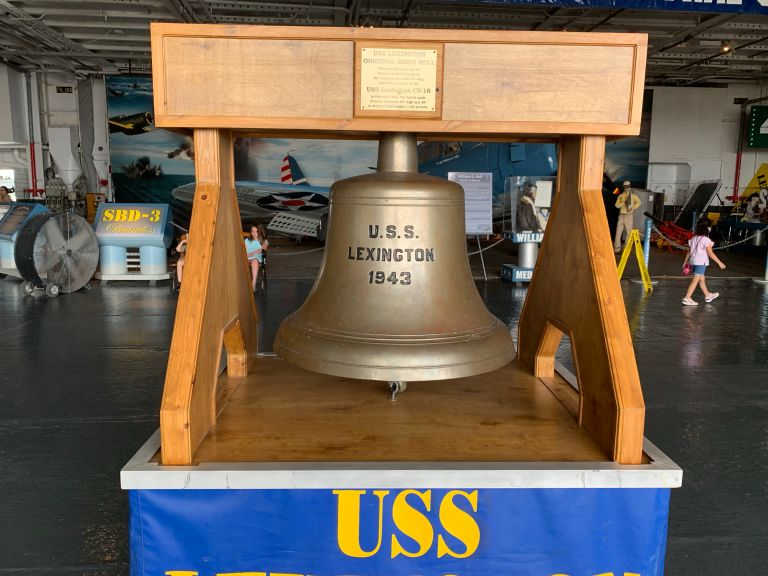 A bell hung on a wooden frame.