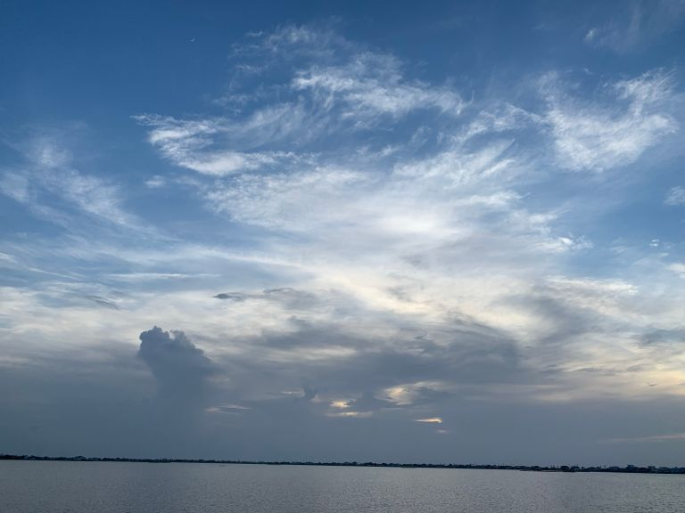 Swirly clouds at sunset over water.