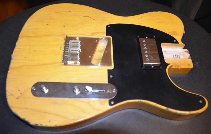 Pickguard, pickup and control plate all screwed down with aged screws