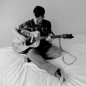 Boz with guitar on bed
