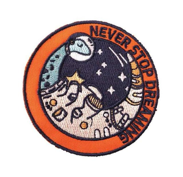 """Embroidered patch design of a sauropod dinosaur in astronaut gear. Reading """"never stop dreaming"""""""