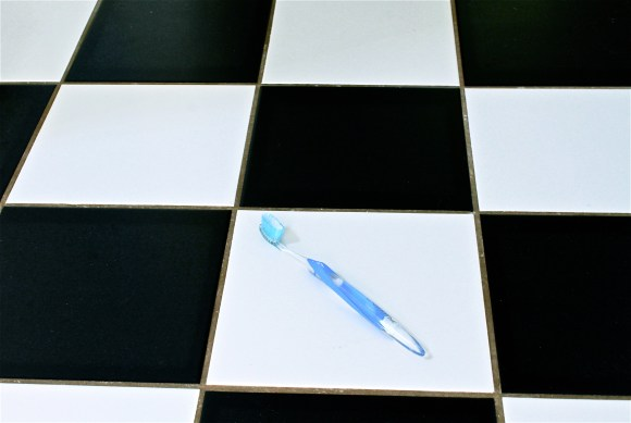 Toothbrush on black and white tiled floor.