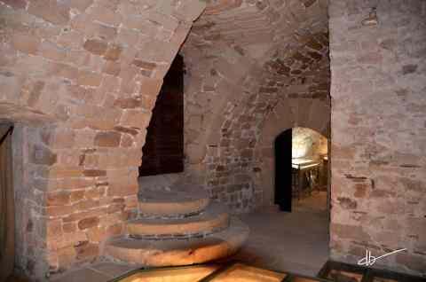 Vue sur l'escalier de la salle des gardes éclairé par une lumière venant du sol