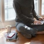 woman in gray sweat shirt sitting beside window
