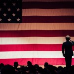 man standing on stage with big American flag