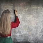 school teacher writing on chalk board