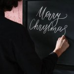 person in black long sleeve shirt writing on black board