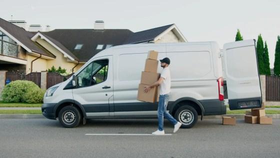 man in white t shirt and blue denim jeans standing beside white van