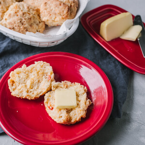 A picture of a pimento cheese biscuit on a plate with butter and a basket of pimento cheese biscuits in the back