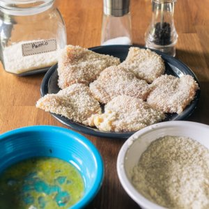 a picture of chicken breaded with panko crumbs, with a bowl of egg wash and a bowl of panko crumbs