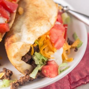 a close up picture of ground beef tacos in fried flour tortilla shells on a white plate