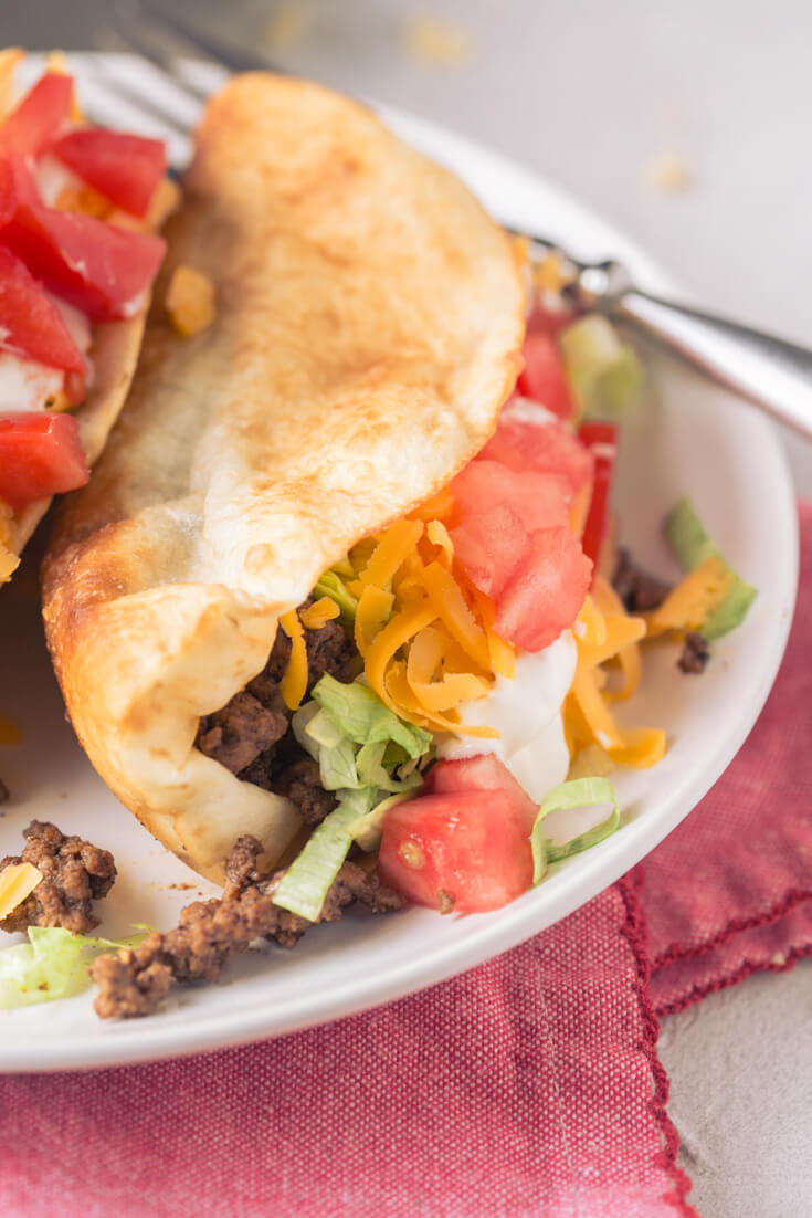 a close up photo of a ground beef taco in a fried flour tortilla shell