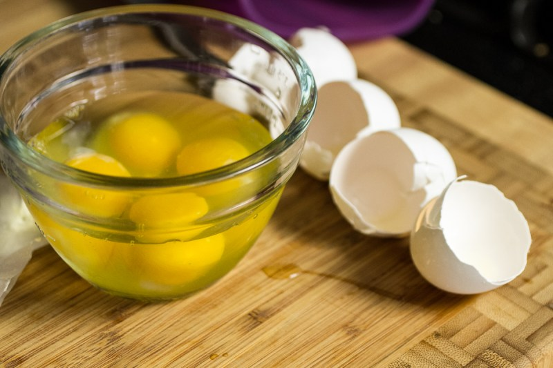 a photograph of eggs in a bowl and eggshells