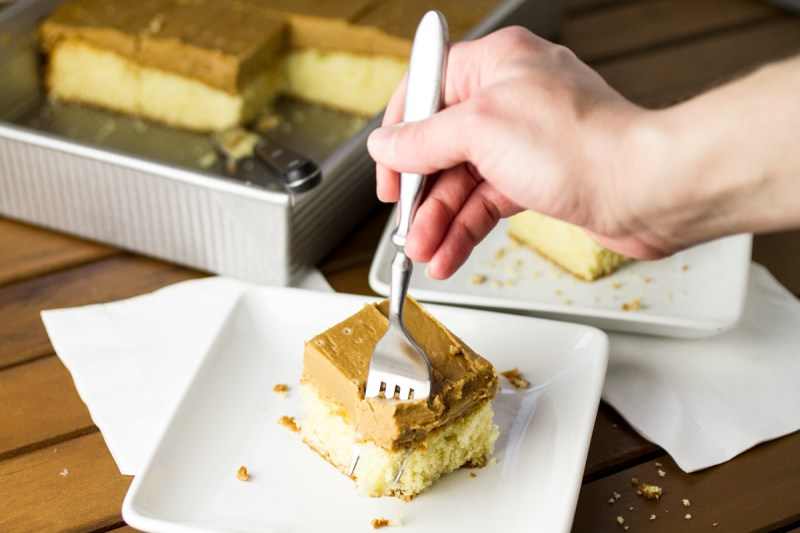 a photograph of a person sticking a fork into a slice of caramel sheet cake