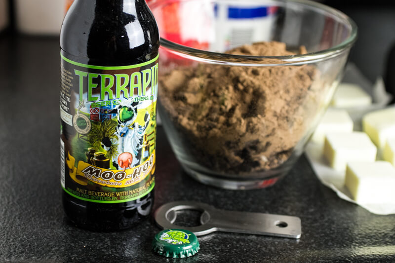 a photograph of a bowl of dry cake ingredients, butter, and a bottle of chocolate milk stout