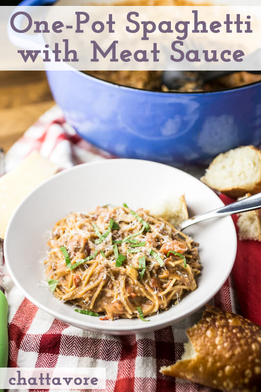 a photograph of a bowl of one-pot spaghetti with meat sauce topped with cheese and basil, with bread and a pot of spaghetti in the background